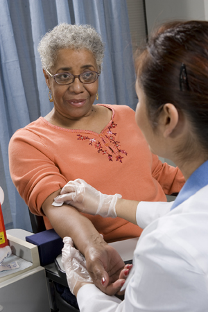 Healthcare provider taking blood sample from woman's arm.