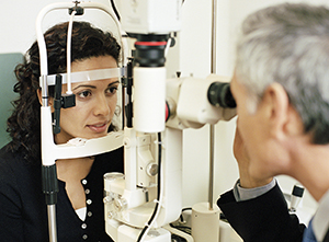 Healthcare provider examining woman's eye.