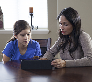 Woman and teen girl looking at electronic tablet.