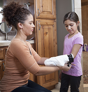 Woman helping girl cover cast on arm with plastic bag.
