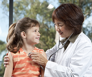 Doctor listening to girl's chest with stethoscope.