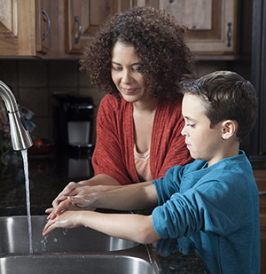 Woman helping boy wash hands in kitchen sink.