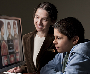 Healthcare provider showing teen boy pictures of his teeth on computer monitor.