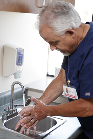 Healthcare provider washing hands in sink.